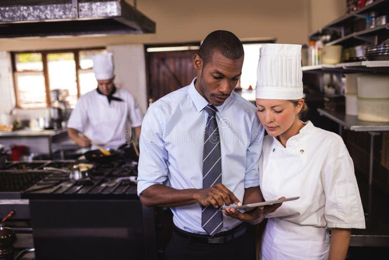 Encargado de sexo masculino y cocinero de sexo femenino que usa la tableta digital en cocina foto de archivo