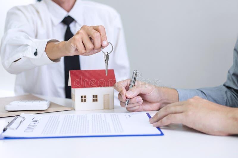 Encargado de ventas de las propiedades inmobiliarias que da llaves al cliente después de firmar imágenes de archivo libres de regalías