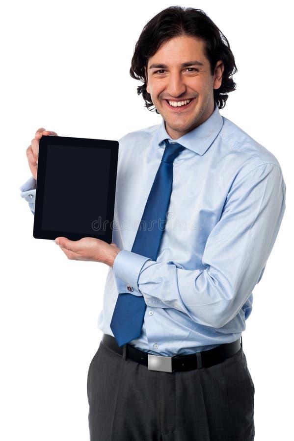 Encargado de ventas que exhibe la PC nuevamente lanzada de la tableta imagen de archivo