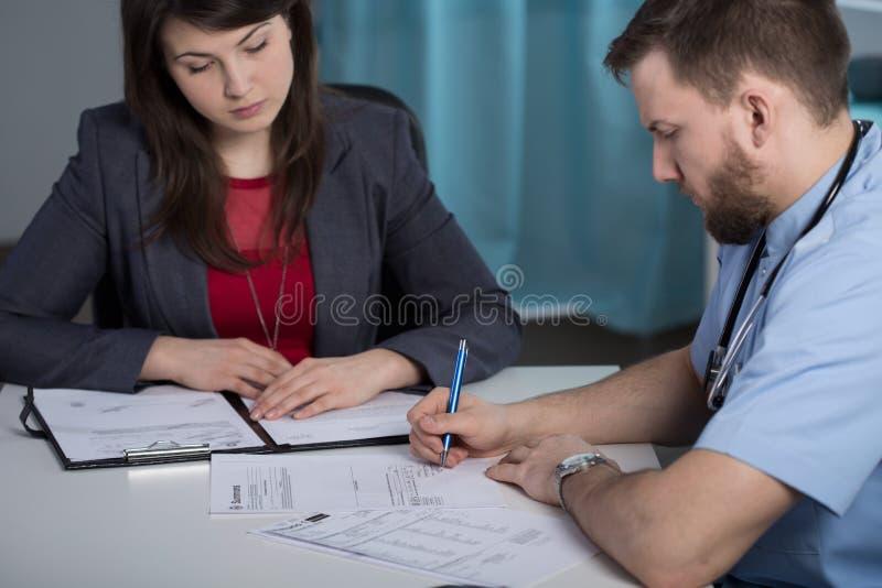 Encargado del hospital que habla con el médico imagen de archivo