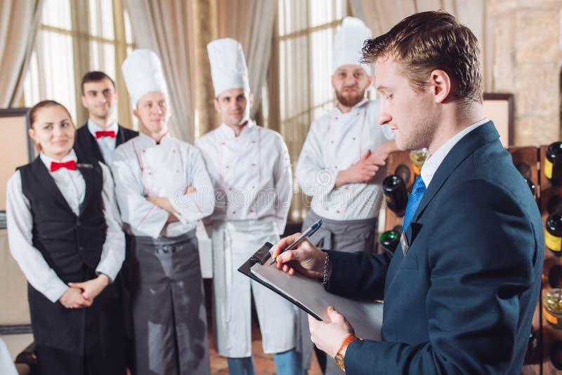 Encargado del restaurante y su personal en cocina el obrar recíprocamente al chef en cocina comercial imagenes de archivo