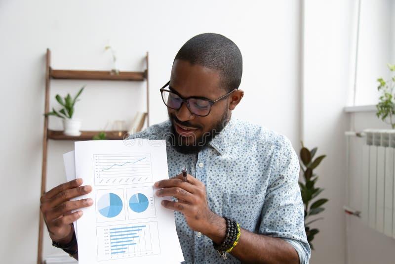Encargado ejecutivo afroamericano sonriente que hace cartas de las ventas de la demostraci?n de la presentaci?n imagenes de archivo