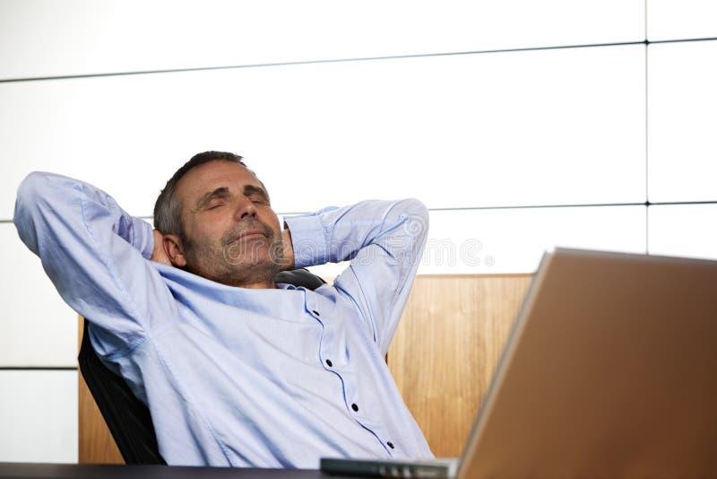 Encargado feliz que se relaja en silla de la oficina. fotos de archivo