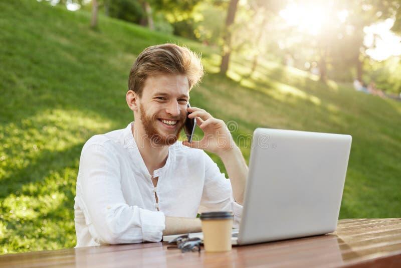 Encargado financiero europeo hermoso joven con el pelo y la barba elegantes, miradas en el monitor del ordenador portátil y el ha imágenes de archivo libres de regalías