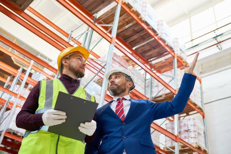 Encargado Giving Instructions al trabajador en Warehouse imagenes de archivo