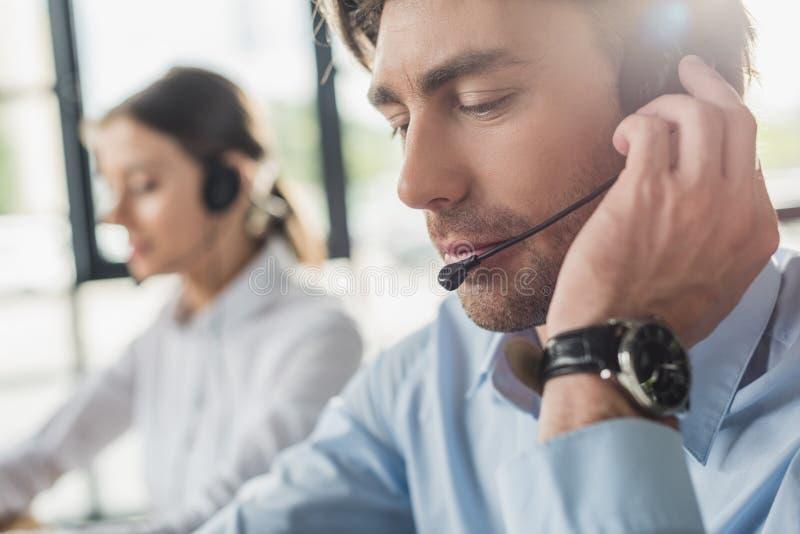 encargado hermoso del centro de atención telefónica en auriculares con el micrófono que se sienta en el lugar de trabajo mientras fotografía de archivo