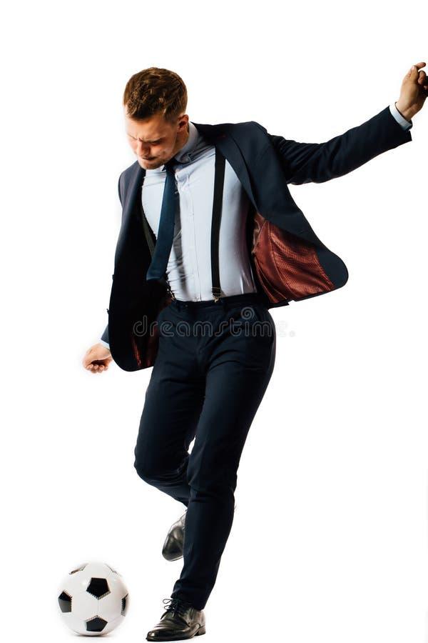 Encargado hermoso joven del hombre de negocios que golpea un balón de fútbol con el pie en el fondo blanco aislado imagen de archivo