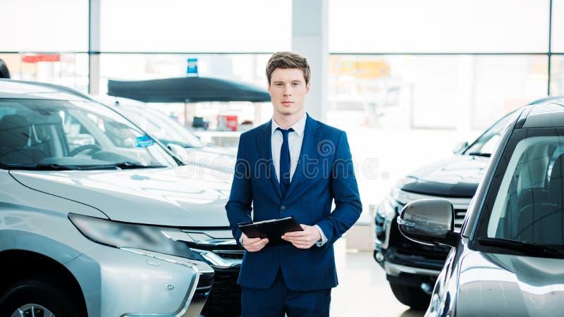 Encargado hermoso que se coloca entre los coches en la sala de exposición del coche y la mirada fotografía de archivo libre de regalías