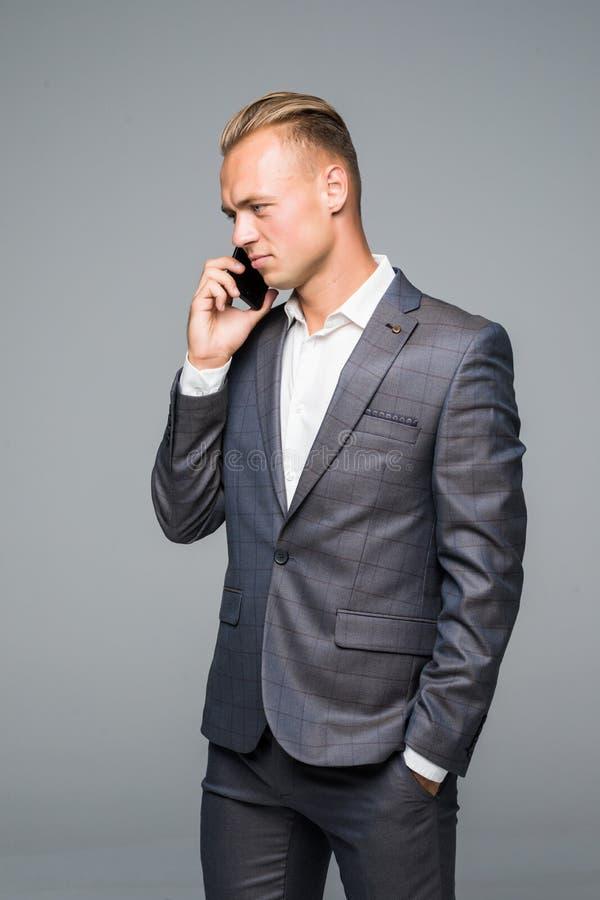 Encargado, hombre u hombre de negocios hablando en smartphone o el teléfono móvil en traje elegante en fondo gris Tecnología para imagen de archivo