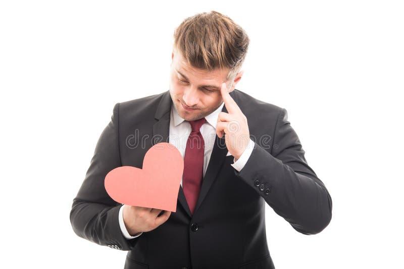 Encargado joven que piensa y que lleva a cabo forma roja del corazón fotografía de archivo