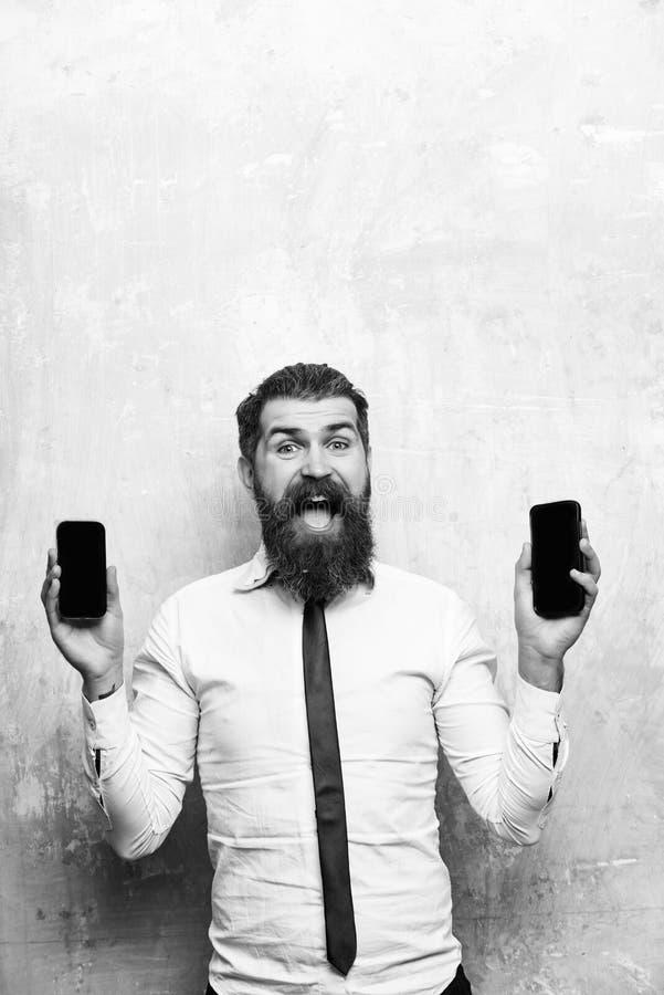 Encargado medio el encargado o el hombre barbudo compara el teléfono móvil y el smartphone fotografía de archivo