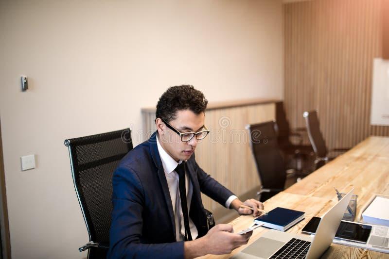 Encargado profesional de sexo masculino que comprueba el email en el teléfono móvil durante día del trabajo fotos de archivo libres de regalías