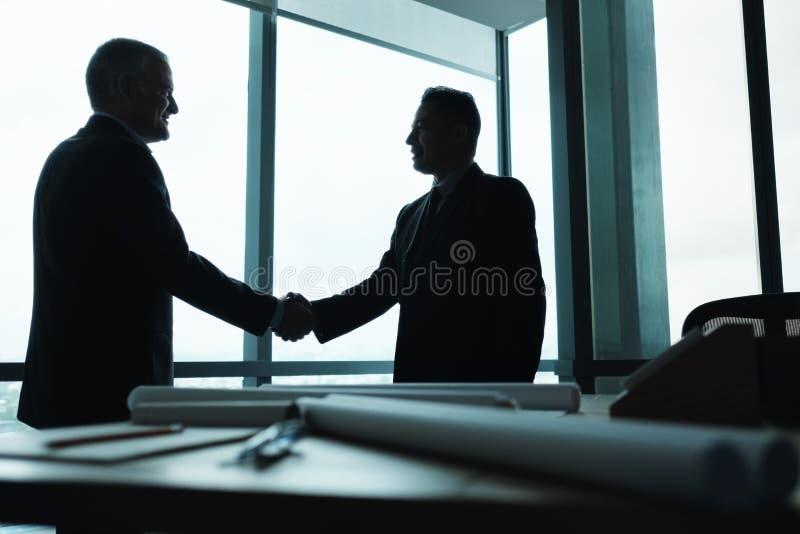 Encargado Shaking Hands del socio comercial en sala de reunión imagen de archivo