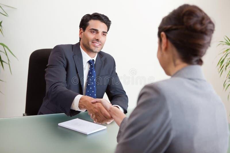 Encargado sonriente que se entrevista con a un candidato femenino imagenes de archivo