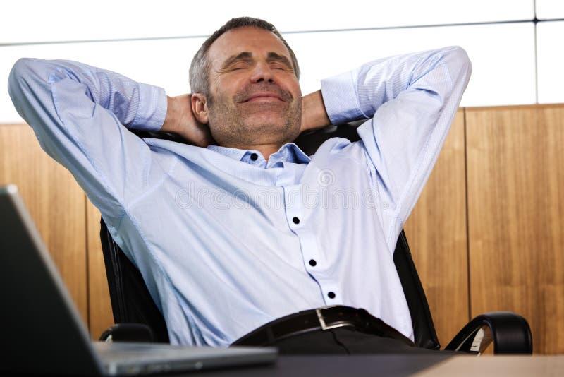 Encargado sonriente que se relaja en silla de la oficina. imagen de archivo libre de regalías