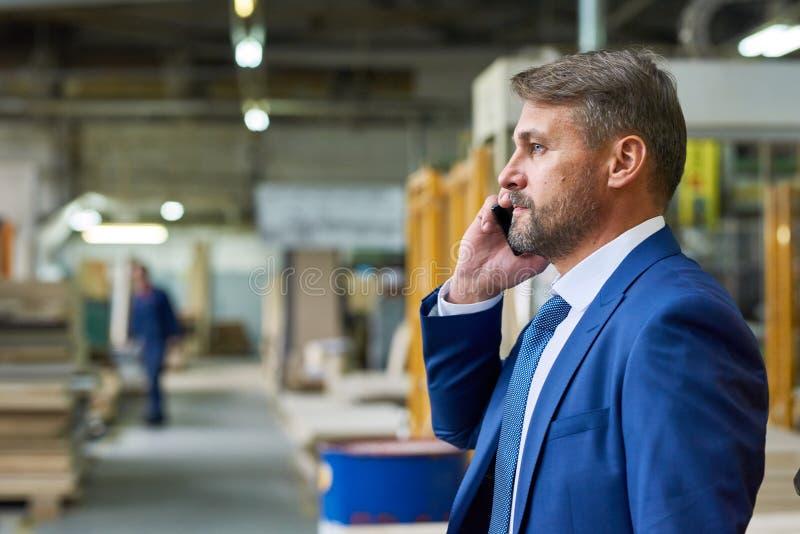 Encargado Speaking por el teléfono en fábrica foto de archivo
