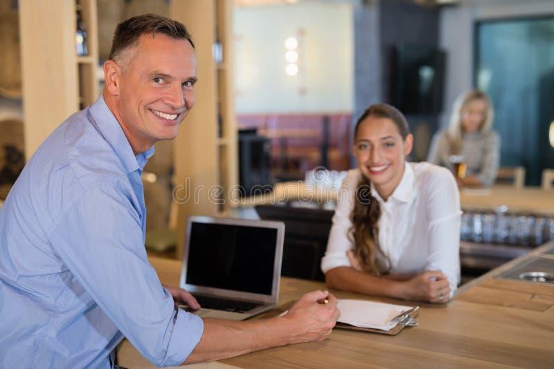 Encargado y camarero sonrientes que se colocan en el contador de la barra fotos de archivo libres de regalías