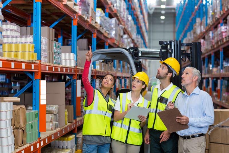 Encargado y compañeros de trabajo de Warehouse que discuten sobre el tablero fotos de archivo libres de regalías