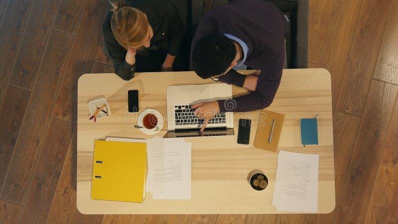Encargado y su colega bastante joven que se sientan en oficina y que trabajan en la presentación del negocio imágenes de archivo libres de regalías