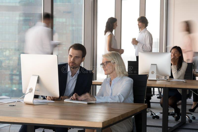 Encargados ejecutivos que trabajan así como el ordenador en oficina corporativa moderna fotografía de archivo