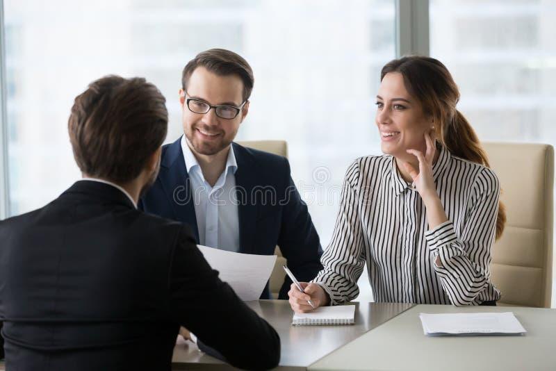 Encargados emocionados de la hora que sonríen teniendo gusto del candidato de trabajo masculino durante la internacional imágenes de archivo libres de regalías