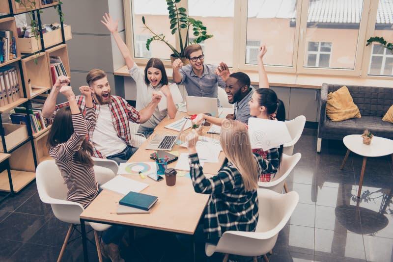 Encargados felices emocionados jovenes que celebran la victoria en la reunión foto de archivo