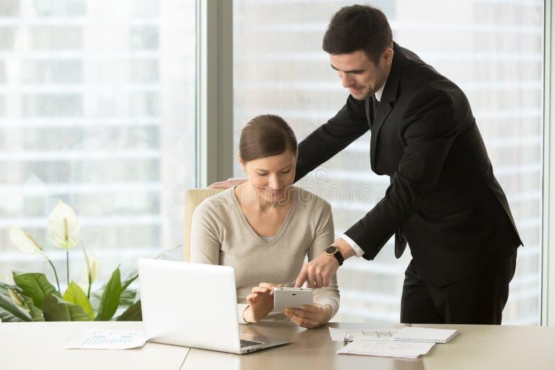 Encargados sonrientes que trabajan en la tableta, agentes usando las propiedades inmobiliarias app fotografía de archivo