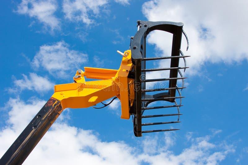 Encavateur agricole de transitoire contre le ciel bleu vif images libres de droits