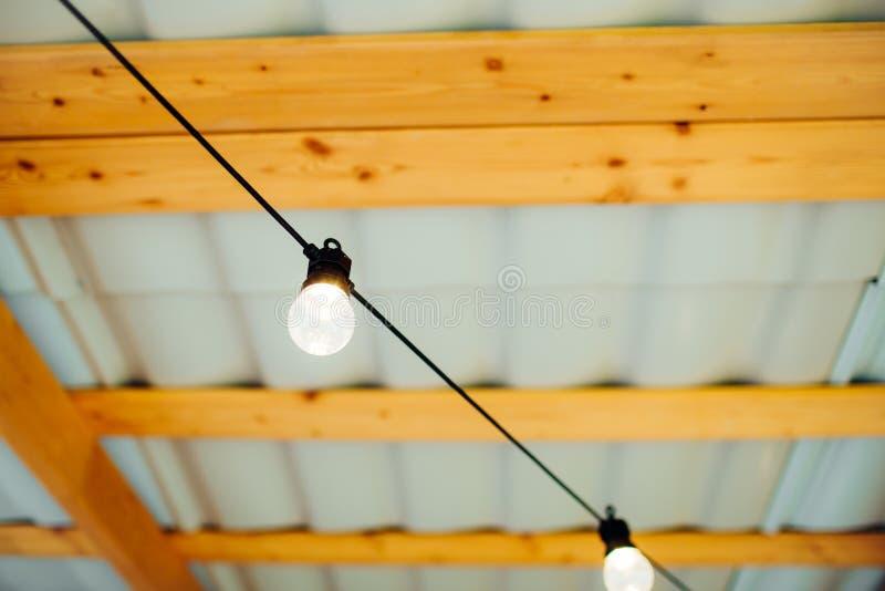 Encendido (con.) bulbos con el fondo de madera imágenes de archivo libres de regalías