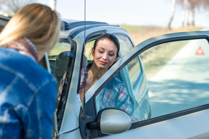 Encendiendo el coche roto dos las mujeres tienen problemas fotografía de archivo libre de regalías