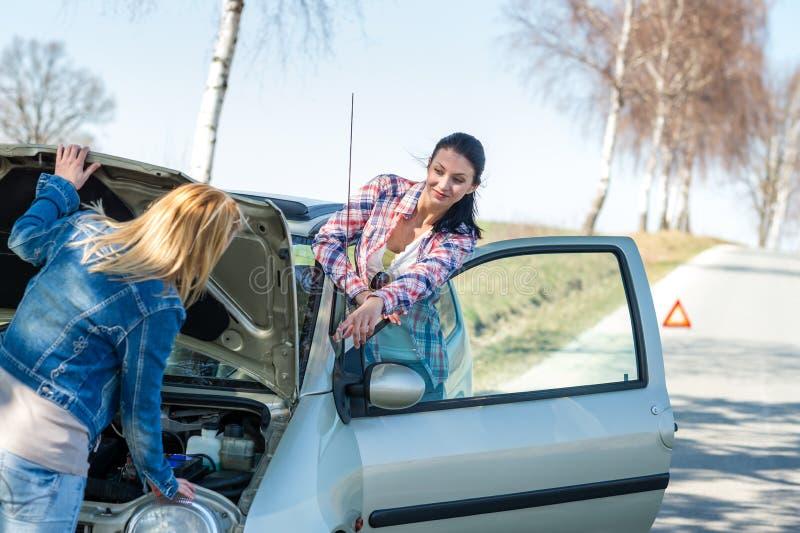 Encendiendo el coche roto dos las mujeres tienen problemas fotografía de archivo