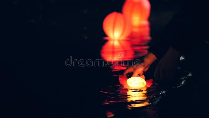 Encendiendo las linternas flotantes de la iluminación en el río en la noche - festival romántico fotografía de archivo libre de regalías