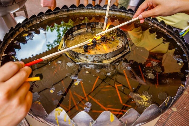 Encens brûlant pour l'usage d'adorer l'image de Bouddha dans le temple, foyer sélectif de la Thaïlande images stock