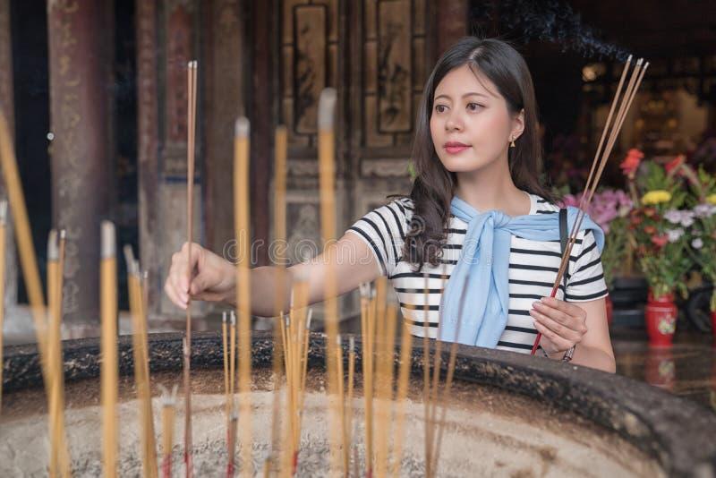 Encens de offre de femme assez asiatique aux dieux images libres de droits