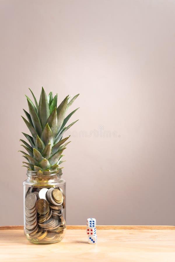 encentmynt i glasflaskan med ananas spricker ut på översidan och tärnar på andra sidan royaltyfria foton