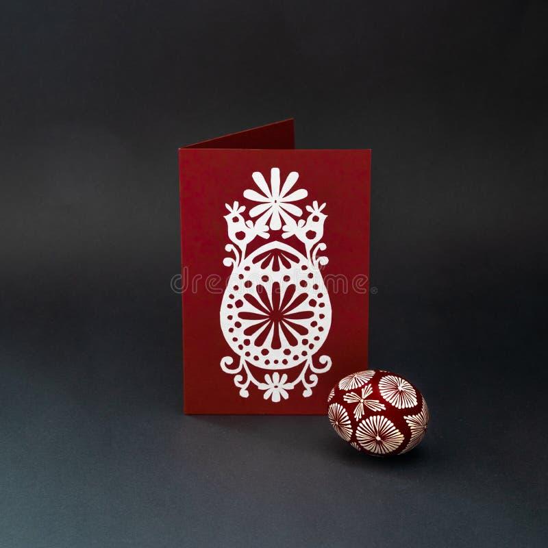 Encere para resistir o ovo da páscoa e o cartão tingidos com papel-corte em um fundo preto imagens de stock royalty free