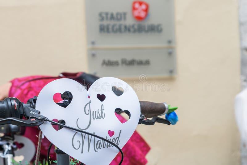 Encerramento de uma bicicleta decorada com joias de casamento em frente à antiga secretaria de Regensburg com o sinal e o alemão fotos de stock royalty free