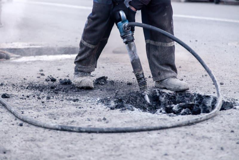 Encerramento de uma fotografia de trabalhadores profissionais na estrada de asfalto, de reparação uniforme, com um martelo Concei fotos de stock royalty free