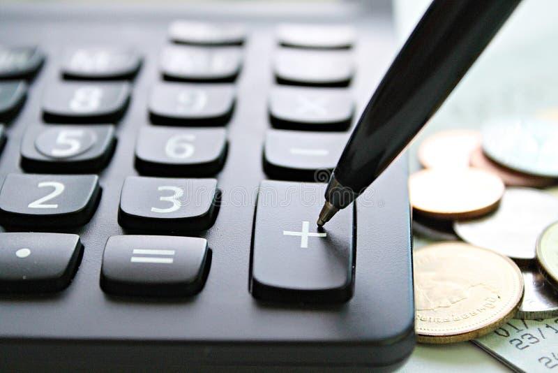 Encerre a imprensa na calculadora positiva do botão e as moedas na tabela da mesa de escritório foto de stock
