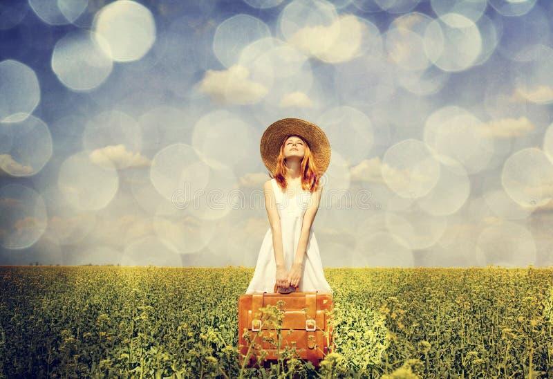 Enchanteresse rousse avec la valise au gisement de graine de colza de source. photo libre de droits