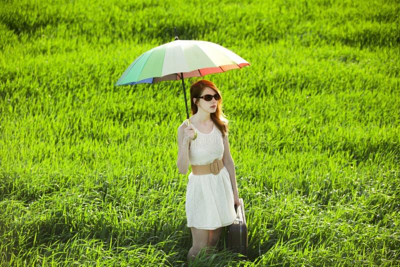 Enchanteresse rousse avec le parapluie et la valise au pays de ressort photo stock