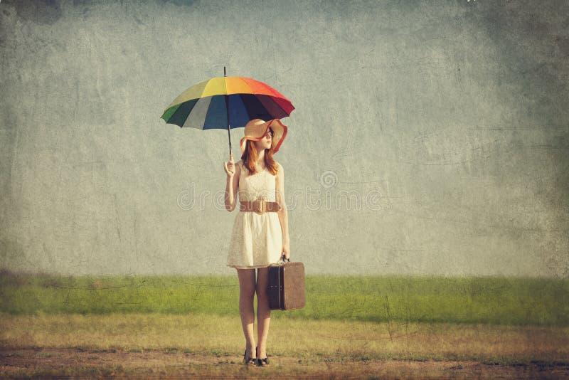 Enchanteresse rousse avec le parapluie et la valise au pays de ressort images stock