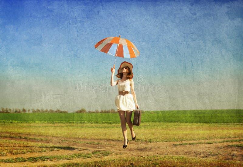 Enchanteresse rousse avec le parapluie et la valise au pays de ressort photos stock