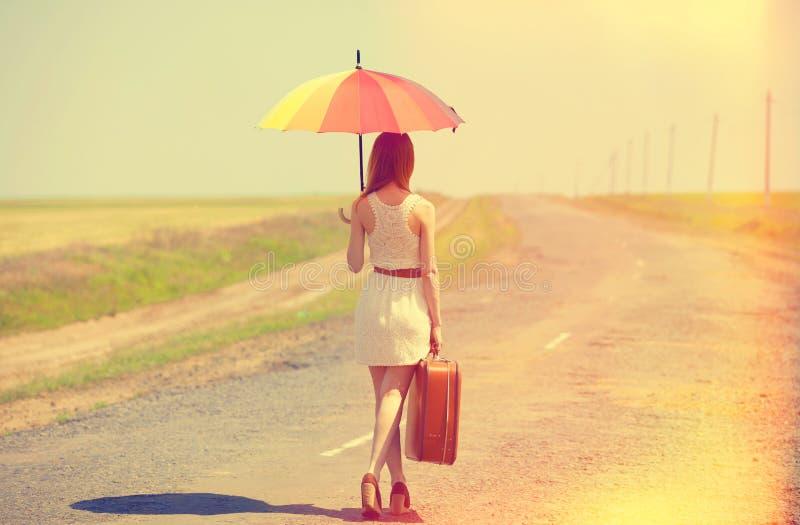 Enchanteresse rousse marchant sur la route photo stock