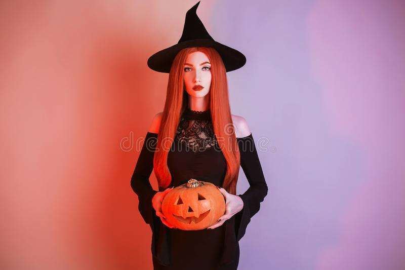 Enchanting halloween costume. Gothic woman witch with pale skin and red hair in black dress holding jack pumpkin. Girl witch with. Red lips. Gothic look stock photo