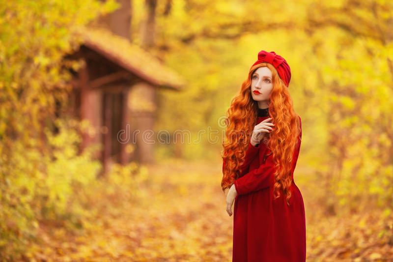 Enchanting redhead woman with long wave hair in red dress on autumn background. Girl on fabulous background of forest with orange. Autumn leaves. Enchanting royalty free stock image