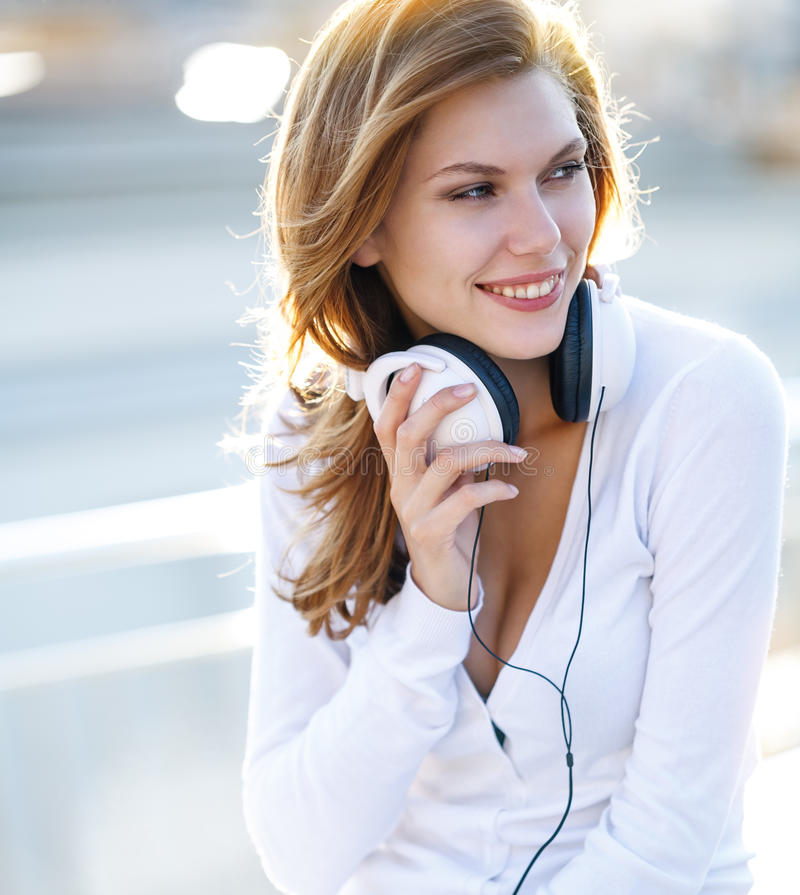 Enchanting young woman holds the headphones. Smiling brunette girl in white clothes with white headphones looking to the side stock photo