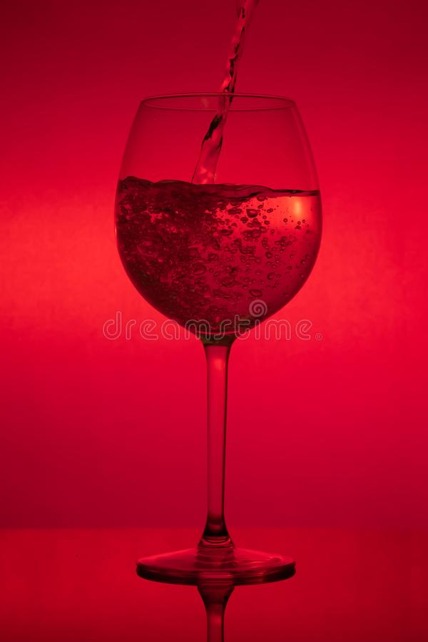 Enchendo o vidro, copo de vinho de derramamento no fundo vermelho foto de stock royalty free