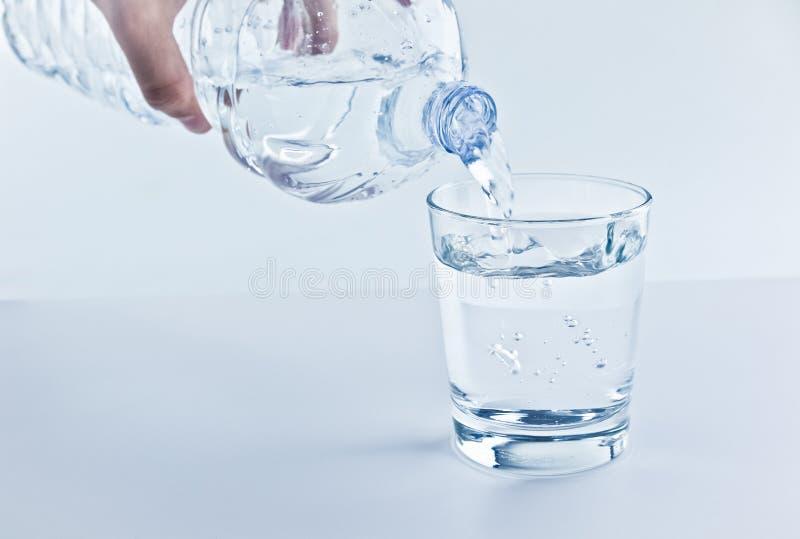 Enchendo um vidro com água com o conceito da garrafa, da nutrição e dos cuidados médicos imagens de stock