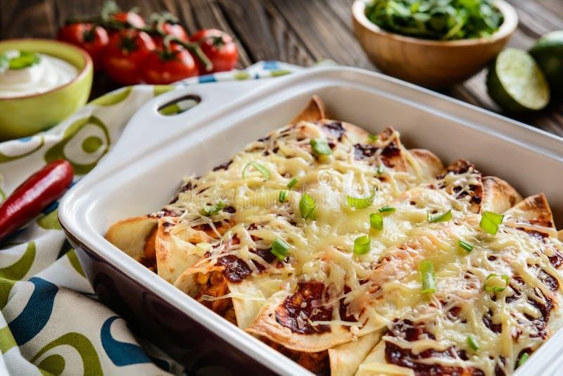 Enchiladas del pollo con salsa al pomodoro, mais, i fagioli ed il formaggio piccanti fotografia stock libera da diritti
